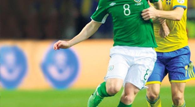Sweden's Sebastian Larsson and Ireland's James McCarthy battle for possession during the World Cup 2014 qualifier in Stockholm