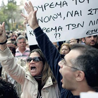 Employees of Cyprus Popular Bank chant slogans outside the Cypriot parliament in Nicosia, while inside politicians were putting the final touches to a plan to avoid bankruptcy.