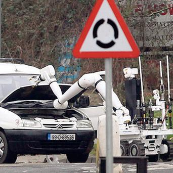 BOMB ALERT: A robot examines a van that was rammed by police in Derry on March 3. Several people were arrested and local homes evacuated.