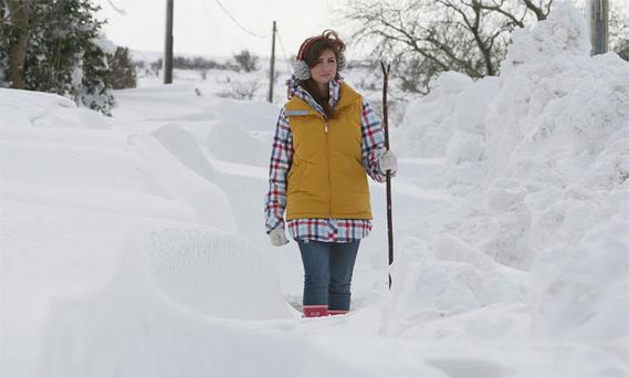 Cara Faith walks through a snow drift near Glenarm, Co Antrim