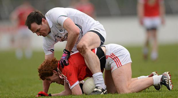 Peter Harte of Tyrone tries to withstand the challenge of Kildare's Michael Foley in St Conleth's Park.