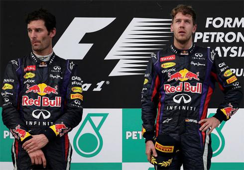 Red Bull Formula One driver Sebastian Vettel (R) and team mate Mark Webber stand on the winners podium after the Malaysian Grand Prix