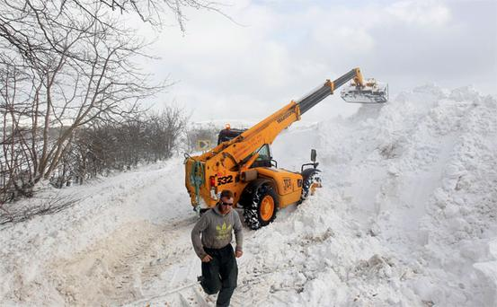 Workmen clear a snow drift blocking the Cushendall Road, in the Glens of Antrim, as wintry weather continues to cause havoc