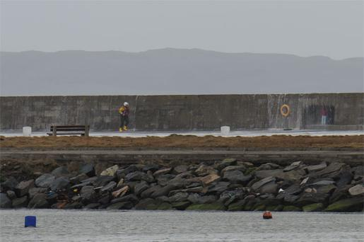 A member of the Howth inshore lifeboat crew approaches the two people trapped in an alcove on Howth pier in Dublin