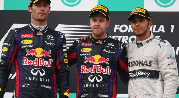 The tension on the faces tells a story as second-placed Mark Webber (left) doesn't warm to the embrace of his Red Bull team-mate and Malaysian Grand Prix winner, Sebastian Vettel, alongside third-placed Lewis Hamilton on Sunday's podium