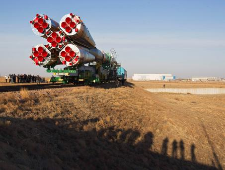 Cameramen cast shadows as the Soyuz TMA-08M spacecraft is transported to its launch pad at the Baikonur cosmodrome.