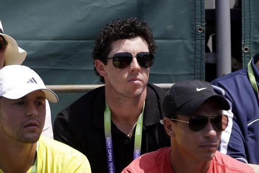 Golfer Rory McIlroy, center, of Northern Ireland, watches the match between Caroline Wozniacki, of Denmark, and Garbine Muguruza, of Spain, during the Sony Open tennis tournament in Key Biscayne, Fla., Saturday, March 23, 2013. (AP Photo/Alan Diaz)