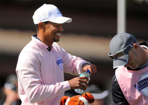 Tiger Woods laughs as he and caddie Joe Lacava wait to start play at the 2013 Tavistock Cup golf tournament at Isleworth Golf and Country Club in Windermere, Florida