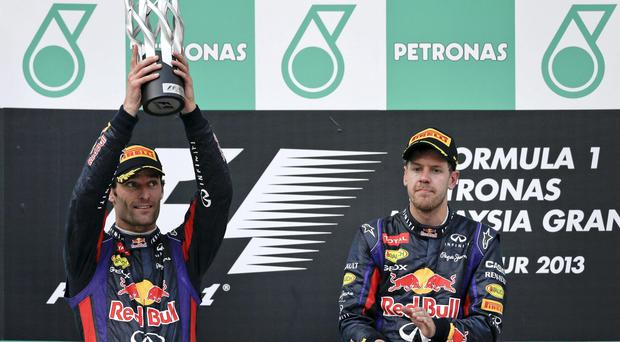 Mark Webber, left, lifts his runner-up trophy while his teammate and the winner Sebastian Vettel applauds at Malaysian Formula One Grand Prix