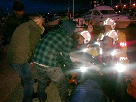 Volunteer lifeboat crew with Fenit RNLI work with locals to help save a stranded dolphin in the Kerry town, after it was washed up on a remote beach.