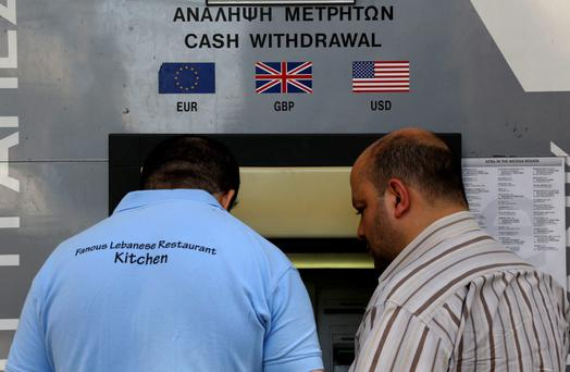 People make transaction at an ATM outside a branch of Laiki Bank in the tourist area of the old district of Nicosia March 27, 2013.