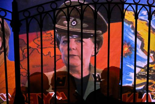 A banner featuring German Chancellor Angela Merkel dressed as German soldier is placed by protesters at the fence of the Presidential Palace during an anti-bailout rally in Nicosia March 27, 2013