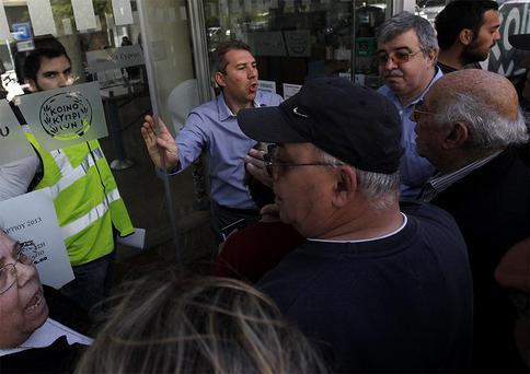 Customers wait outside a branch of Bank of Cyprus before it opened in Nicosia