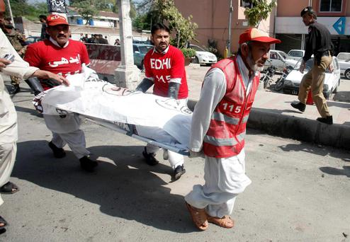 Rescue workers carry away a body of a man from the site of a bomb blast in Peshawar March 29, 2013.