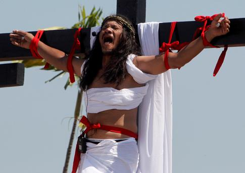 Ruben Enaje, 52, who is portraying Jesus Christ for the 27th time, screams as he hangs on a wooden cross during a Good Friday crucifixion re-enactment in San Pedro Cutud town, Pampanga province, north of Manila March 29, 2013.