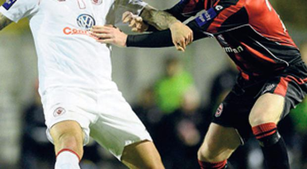 Anthony Elding battles it out with Stephen Paisley at Dalymount Park