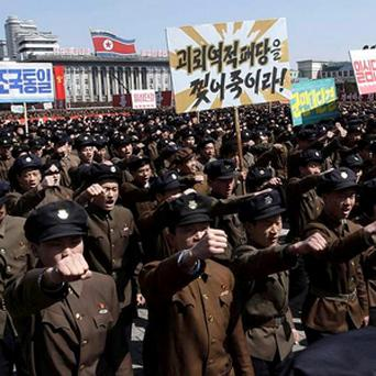 North Koreans march through Kim Il Sung Square in downtown Pyongyang, North Korea, Friday