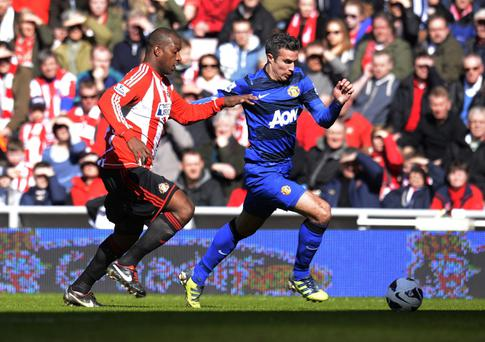 Manchester United's Robin Van Persie and Sunderland's Titus Bramble (left) battle for the ball during the Barclays Premier League match at the Stadium of Light