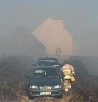 Firefighters rush through the smoke to prevent a gorse fire spreading to a house in Co Clare