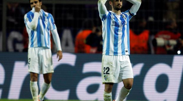 Malaga's Isco (R) walks from the pitch dejected after defeat to Borussia Dortmund