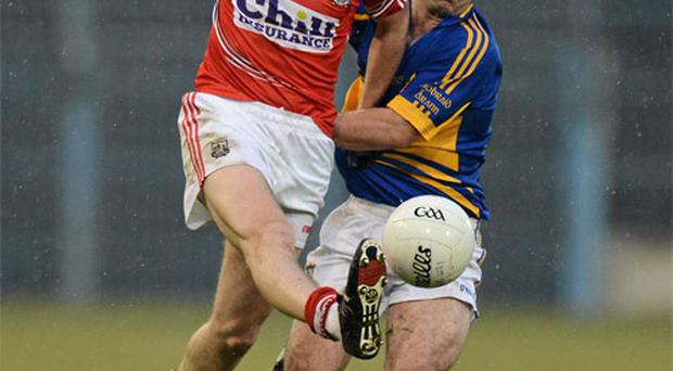 Mark Surgue on the charge for Cork despite the close attention of Tipperary's Paddy Dalton.