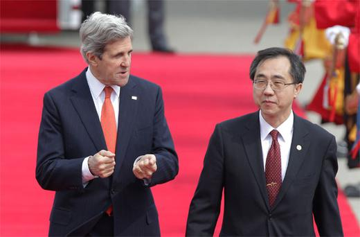 John Kerry walks with deputy director general of South Korea's Foreign Ministry Moon Seoung-hyun upon his arrival in Seoul