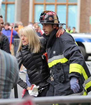 An injured woman is attended to at the scene of an explosion at the Boston Marathon