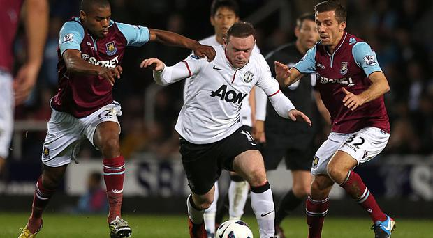 Manchester United's Wayne Rooney (centre) battles for the ball with West Ham United's Gary O'Neil (right) and Ricardo Vaz Te (left)