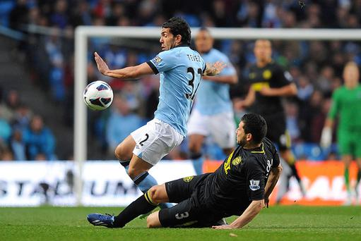 Wigan Athletic's Antolin Alcaraz (right) slides in on Manchester City's Carlos Tevez (left)