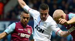 Robin van Persie of Manchester United battles for the ball with Winston Reid (L) and James Collins of West Ham United during the Premier League match between West Ham United and Manchester United at the Boleyn Ground. Picture: Jamie McDonald/Getty Images.
