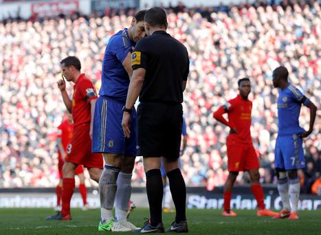Chelsea's Branislav Ivanovic shows his arm to referee Kevin Friend after an incident with Liverpool's Luis Suarez
