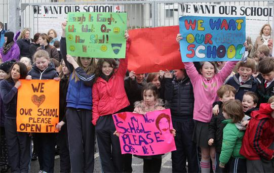 Children and parents protest yesterday outside the unfinished St Anne's National School, inset left, in Ardclough, Co Kildare