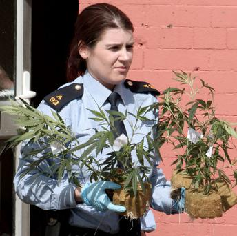 A garda leaves the house in Inchicore.