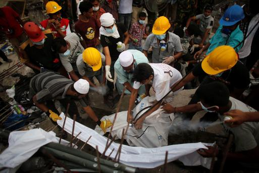 Rescue workers bring out the remains of a garment worker from the rubble of the collapsed Rana Plaza building, in Savar, 30 km (19 miles) outside Dhaka