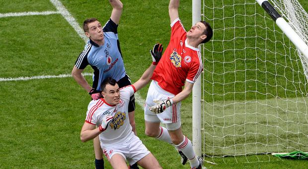 Tyrone goalkeeper Niall Morgan and team-mate Cathal McCarron in action against Jason Whelan