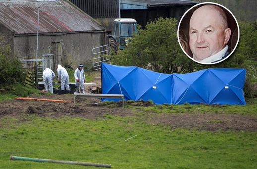 Garda forensics officers examining the slurry tank where the body was discovered at the back of the farm in Fawnagown outside Tipperary town