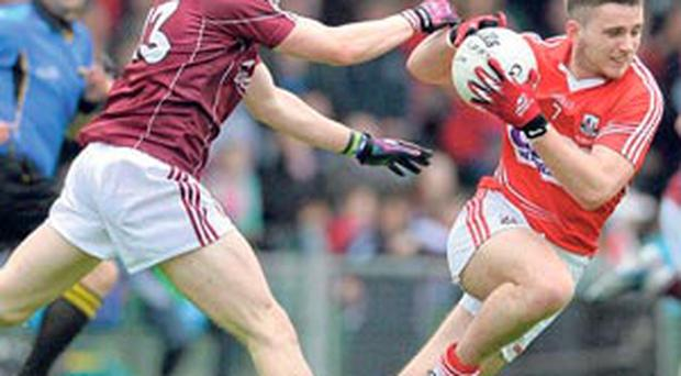 Cork's Jamie Wall tries to escape the challenge of Shane Walsh.