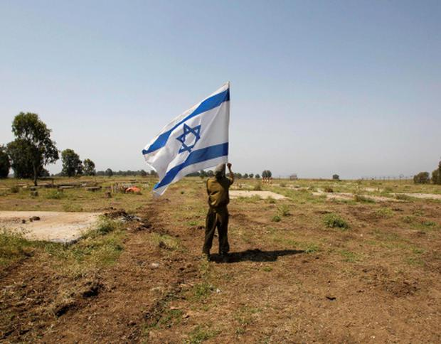 An Israeli soldier places a flag close to the ceasefire line between Israel and Syria on the Israeli occupied Golan Heights. Photo: Reuters