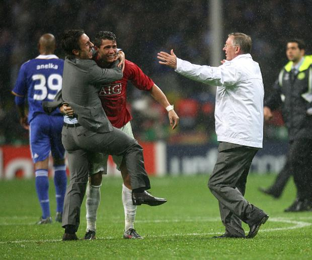 Ferguson runs onto the pitch to congratulate Cristiano Ronaldo with Gary Neville after winning the Champions League in Moscow