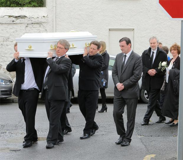 The parents of Emily Wilson (10) Nick Wilson and Caitriona Clutterbuck walk hand in hand as they follow her coffin after funeral Mass in the Church of the Sacred Heart in Gortnahoo, Co. Tipperary.