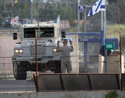 A United Nations peacekeeper directs an armoured vehicle after it crossed from Syria to the Israeli-occupied Golan Heights at the Kuneitra border crossing