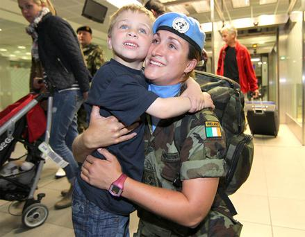 Four year old Neil Lardiner welcomes his aunt Lt Deirdre Newell after she arrived in to Dublin airport