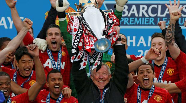 Manchester United manager Alex Ferguson lifts the Premier League trophy as his players celebrate in his final game at Old Trafford