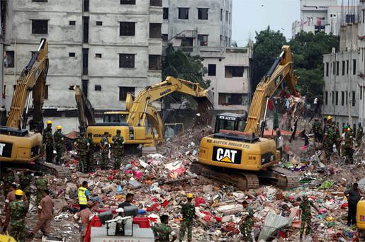 Bangladeshi rescuers use heavy machinery to clear rubble of a garment factory building that collapsed on April 24