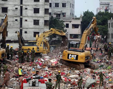 Bangladeshi rescuers use heavy machinery to clear rubble