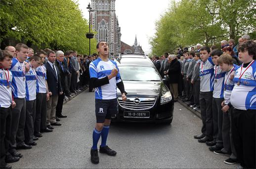 Dan Cournane from Tralee Rugby Club, who was coached by Donal Walsh (inset), performs a funeral haka as Donal's remains are brought from St John's Church in Tralee, Co Kerry. Munster rugby stars helped carry the coffin