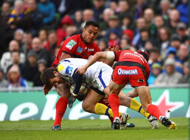 Clermont's Brock James (C) is tackled by Toulon's Chris Masoe (L) and Matt Giteau (R)