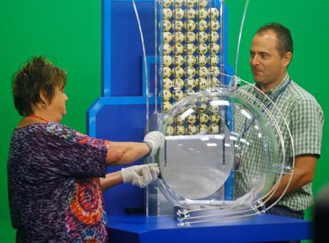 Terri Chick (L) and Chris Desmarais of the Multi-State Lottery Association prepare the balls used in the Powerball drawing at the Florida Lottery studio in Tallahassee May 18, 2013. They are using gloves to prevent the oil on their hands from contaminating the balls, which could change their weight.