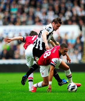 Mathieu Debuchy (C) of Newcastle in action against Kieran Gibbs (R) and Tomas Rosicky of Arsenal