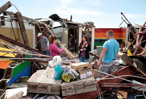 Teacher's assistant Amber Ford takes a photo of first grade teacher Sheri Bittle after finding items inside Bittle's classroom at Briarwood Elementary School after the building was destroyed by yesterday's tornado on May 21, 2013 in Moore, Oklahoma.